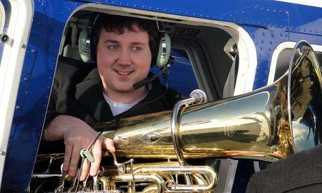 Tuba player John Whitener boarding the plane to Foula, on Friday morning.