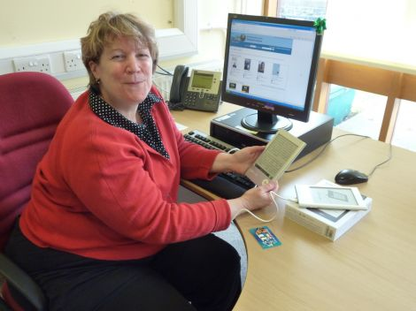 Librarian Marghie West tries out an eReader. Pic. SIC