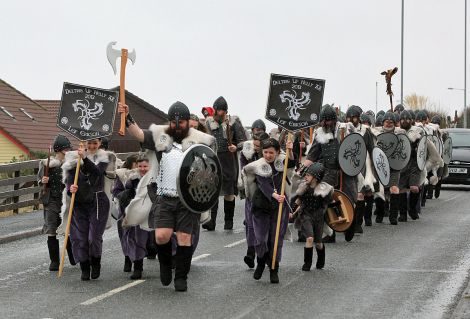 Delting Up Helly Aa Jarl's Squad hit by a wintry shower while marching through Brae on Friday morning.