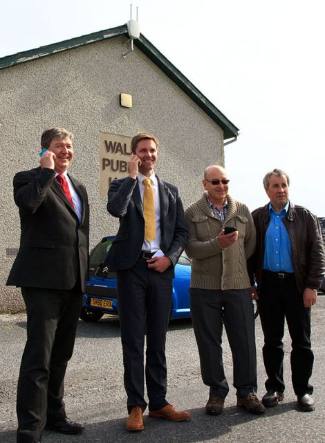 Getting connected in Walls (from left to right): isles MP Alistair Carmichael, John McCracken of Vodafone, as well as Doug Forrest and Ian Walterson of the Sandness and Walls Community Council - Photo: Olivia Abbott/ShetNews