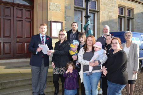 Urafirth parents handing over a petition calling on the SIC to save their school on Monday. Photo: Shetnews/Neil Riddell