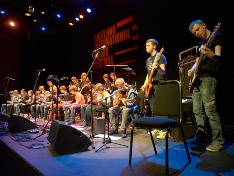 """High Level Music students packing the stage at the festival-closing """"guitar heroes"""" concert. Photo: Chris Brown"""