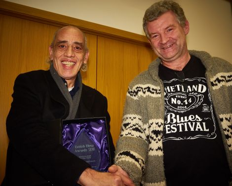 Norman Watt-Roy receives the British blues award for best bass player in 2015 from Shetland Blues Festival organiser Jimmy Carlyle - Photo: Chris Brown