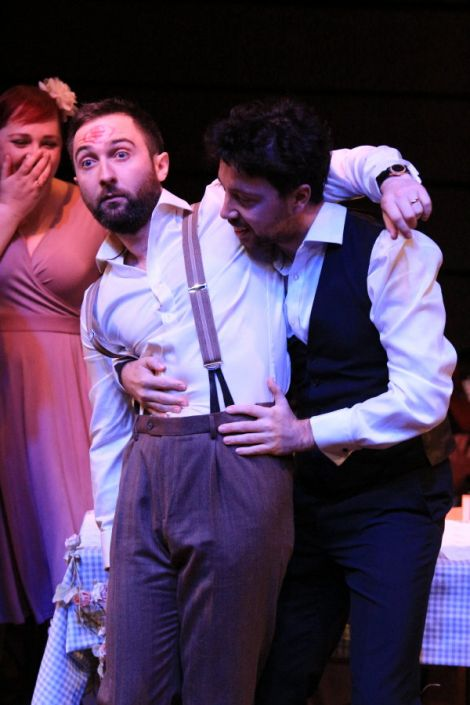 Andrew Dickenson (Iain) is carried by Douglas Nairn (Alasdair) with soprano Shuna Sendall (Elsa) in the background.