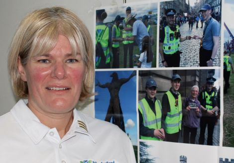 PC Carole Smith with photos of some of the young volunteers elsewhere in Scotland. Photo Chris Cope/Shetnews