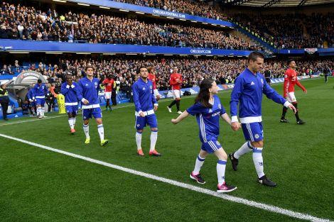 Mascot Macy coming out onto the Stamford Bridge turf alongside Cesar Azpilicueta.