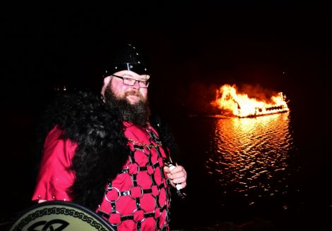 Northmavine guizer jarl Liam Doull witnesses his galley disappearing - Photo: Mark Berry