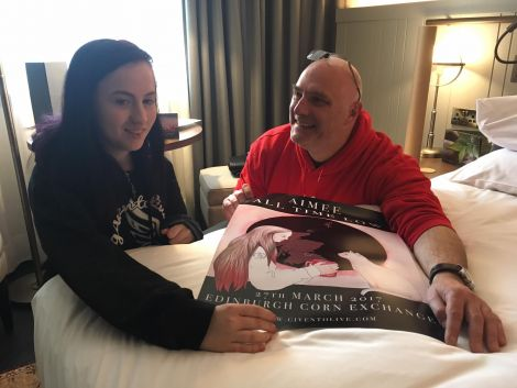 Aimee with Tom Pugh of the non-profit group Given to Live and a personalised gig poster ahead of her first ever live concert experience.