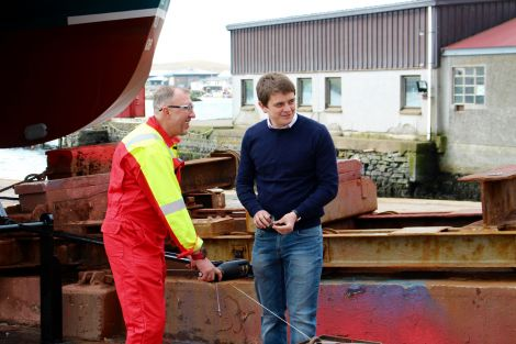 Malakoff's Ryan Stevenson (right) preparing the champagne bottle before it was smashed against the boat.