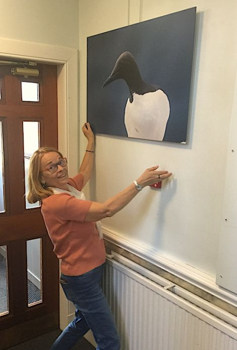 Georges Dif's widow Nelly hanging one of his photos at Islesburgh Community Centre last week. Photo: Jonathan Wills