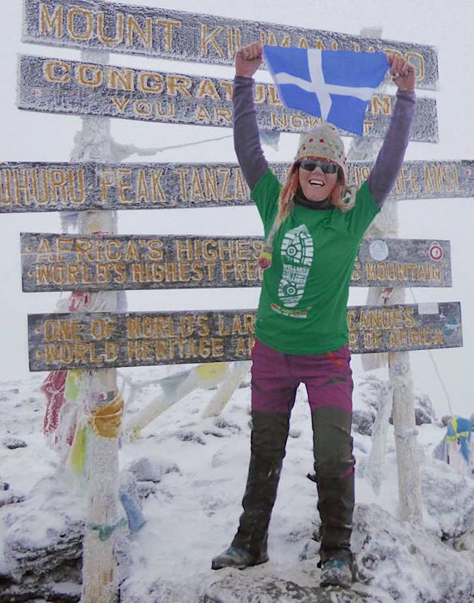 Anita Georgeson unfurling the Shetland flag at top of Africa.